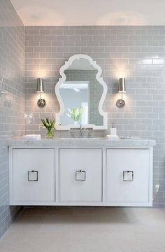 White floating washstand fitted with square polished nickel pulls and a white marble countertop holding a rectangular sink fitted with a polished nickel faucet positioned under a Jonathan Adler Queen Anne Mirror flanked by two polished nickel scones mounted on a floor-to-ceiling gray subway tile backsplash.