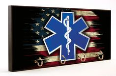 Emergency Medical Service Star of Life Distressed American Flag Key Hanger is found exclusively in our Brotherhood® collection. The bold colors in the design leap off of the wooden surface catching e