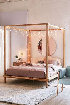 Love the lights hanging from this Eva Wooden Canopy Bed - Urban Outfitters