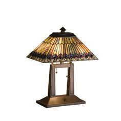 Glowing Amethyst Jewels Circle Stylized Peacock Feathers Made Of Amber, Jade And Amethyst Streaked Plum Colored Art Glass With Cobalt And Plum Accents. Each Piece Of Stained Glass In This Tiffany Style Shade Is Hand Cut And Wrapped In Copper Foil. This Versatile Favorite Is A Match To Many Decorative Styles. The Oblong Table Lamp Base Is Hand Painted In A Beautiful Mahogany Bronze Finish.