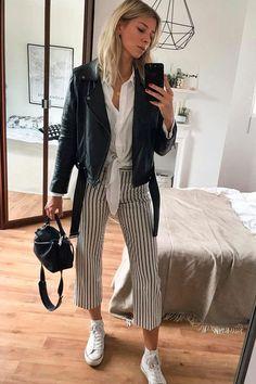 Lindsay Holland usa calça cropped listrada, camisa branca com nó, jaqueta de couro e all star.