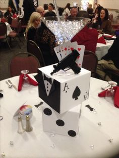 James Bond Casino party pics!  Easy to do!....wrap 8x8x8 cardboard boxes in white craft paper. Add card stock 2 1/2inch dice dots. Dollar store gun painted black and an oversized martini glass filled with water beads. Glue on some playing cards and Voila!