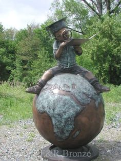 'Boy Reading on Top of the World. bronze statue [sculpture] of boy sitting astride a globe peering at a book through a magnifying glass Public Sculpture, Reading Art, Statue, Book Art Sculptures, Sculpture, Art, Street Art, Garden Art, Top Art Schools