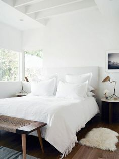 Scandinavian style bedroom featuring white walls, white upholstered headboard and bed linens, black and white framed artwork, a sheepskin rug and a woven seat wood bench - Neutral Home Decor & Decorating Ideas
