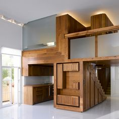 Hogarth Architects transformed an apartment using a wood insert that creates a separated kitchen and loft. Essentially one big piece of custom-made furniture.