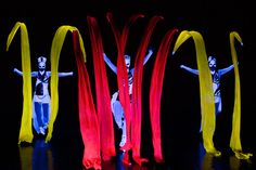 Red and yellow ribbons, dancers under black light in Crystal UV Light Show - Anta Agni.