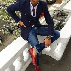 Opt for a dark blue striped double breasted blazer and blue jeans to look classy but not particularly formal. Tap into some David Gandy dapperness and complete your look with red leather tassel loafers.   Shop this look on Lookastic: https://lookastic.com/men/looks/double-breasted-blazer-dress-shirt-jeans/24003   — White Dress Shirt  — Red Polka Dot Pocket Square  — Navy Vertical Striped Double Breasted Blazer  — Brown Leather Belt  — Blue Jeans  — Red Leather Tassel Loafers