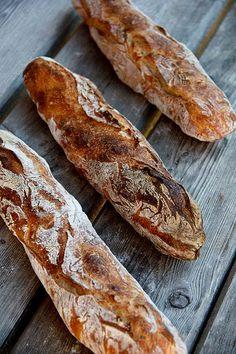 """Mein erstes nur auf Sauerteig basiertes Baguette-Rezept. Beim ersten Versuch im Almkurs war der Teig noch zu fest. Entsprechend schwierig und """"entgasend"""" war das Formen. Mit ausreichend Geduld während der Teigreife entstehen unheimlich aromatische, mild-säuerliche Baguettes mit wilder Porung und sehr langer Frischhaltung. Auch zwei Tage später sind die Baguettes saftig und lecker. Die Sauerteigzutaten … … Weiterlesen →"""
