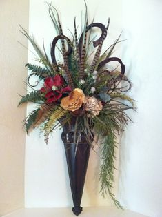 Wondering what to do with your expansive stairway wall? Why not decorate with a pair of gorgeous custom wall sconces. This pair features burgundy red magnolia, cream hydrangea, red hydrangea, tall chocolate brown dried banana sticks, an abundance of pheasant feathers and lot's of greenery. Designed by Amy Johnson - Greatwood Floral Designs.