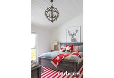 Boldly-striped indoor-outdoor carpeting and bright accents create a Muskoka motif in this bedroom furnished with a king-size bed and a single bed.  http://www.ourhomes.ca/articles/build/article/whitewashed-weekender-ripe-with-rustic-chandeliers