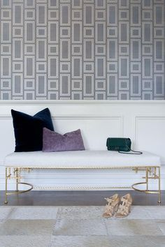 Chic foyer boasts a polished brass bench accented with a white cushion topped with deep blue and purple velvet pillows placed against a white wainscot trim beneath an upper wall covered in gray geometric wallpaper.