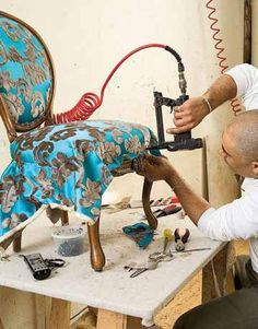 After a layer of duke cotton, blue foam, and Dacron, Matthew applies the fabric.   - CountryLiving.com
