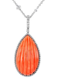 18 karat white gold pendant consisting of 1 tear drop shaped carved coral piece set surrounded by full cut diamond accents, the pendant hangs from an opera length by the yard style necklace set with diamond accents. 1stdibs.com