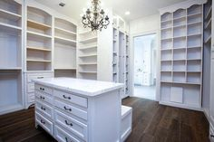 Chic white walk in closet features white built-in shelves and drawers as well as…