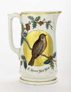 Jug of cream coloured earthenware decorated on both sides with a robin in a gold roundel, with mottoes 'A Merry Christmas' and 'A Happy New Year', by Cochran, Britannia Pottery, Glasgow.