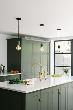 This Shaker kitchen t has been painted in a bespoke shade, a beautiful dark olive that works so well with the aged brass hardware and tap. The three hanging pendant bulbs are a cool addition and add a modern touch to this space. Olive Kitchen, Dark Green Kitchen, Green Kitchen Cabinets, Kitchen Cabinet Colors, Kitchen Colors, Kitchen Colour Schemes, Kitchen Brass Hardware, Color Schemes, Kitchen Cart