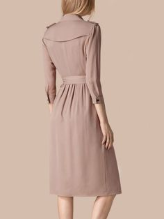 A Burberry trench dress in lightweight silk with a belted waist. Tailored slim through the body in an easy and elegant cut.