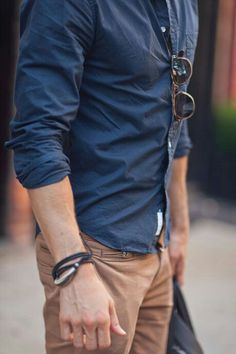 Shop this look on Lookastic:  https://lookastic.com/men/looks/navy-long-sleeve-shirt-khaki-chinos-dark-brown-sunglasses-black-bracelet/10783  — Black Bracelet  — Khaki Chinos  — Navy Long Sleeve Shirt  — Dark Brown Sunglasses