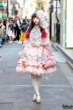 RinRin Doll is a popular Tokyo-based model and YouTuber who we often see around the streets of Harajuku. RinRin is a model for the Japanese lolita brand Angelic Pretty and her sweet lolita look here features all items from Angelic Pretty including a dress, stockings, gold heels, hair decoration, lace gloves, and quilted bow handbag.
