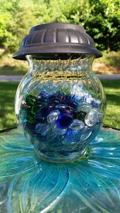 Reuse the top of a solar light add a small vase and glass stones. Very pretty at night.