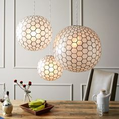 love these little guys - pretty and pearl-y but the hex pattern keeps it modern - Capiz Orb Pendants | west elm