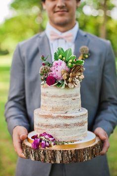 Krásný svatební dort, umístěný na dřevěném podstavci.
