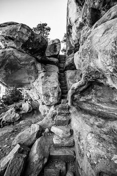 Black and white fine art photograph of one of the rugged hiking trails at Mesa Verde in Colorado. The path travels under huge rock ledges, between massive boilders and walls, past the ancient petrogly
