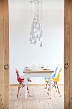 Wnętrze, które uspokaja / jadalnia, biały stół, kolorowe krzesła, biała lampa wisząca