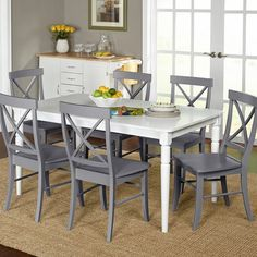 The charming white Brookwood<br/>dining table with rounded corners and turned legs is sure to compliment your decorating style. The six Brookwood cross back dining chairs will keep your room light and airy. The set features solid rubber wood construction.