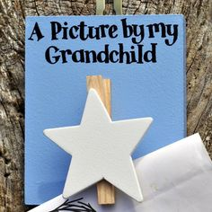 A lovely wooden star peg with lettering: 'A picture by my grandchild'Angelic Hen has a wide range of little pegged out products, please see our products page for other designs.A perfect gift for any proud grandma or grandpa. This lovely hand painted wooden peg with a white star and blue background allows proud grandparents to display their grandchildren's artwork. The pegs are made by our wild Welsh artists in Angelic Hen's beautiful Wye Valley studio. The wooden surround is painted blue…
