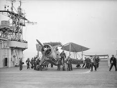 Maintenance crew bringing a torpedo-loaded Fairey Swordfish onto the flight deck of the BATTLER by Hydraulic lift. © IWM (A 16650)