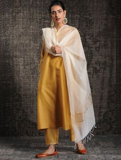 Cast a spell with this Mustard Silk Trouser Suit Which will surely tell them that the diamonds aren't the only beautiful thing which they have seen. This Closed neck and Full Sleeves Party Wear Attire highlighted with zari and dori work. Silk Kurti Designs, Kurta Designs Women, Kurti Designs Party Wear, Designer Kurtis, Indian Designer Suits, Indian Wedding Outfits, Pakistani Outfits, Indian Outfits, Wedding Dresses