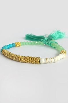A gorgeous statement bracelet with featured turquoise beads, it has lovely gold thread and little aqua tassels to finish it off. Grab a few and make a stack.