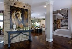 Gorgeous use of artwork in a large space. Love the horse painting on the stone wall. Rustic wood floors are gorgeous.