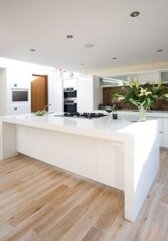 White waterfall countertop. Brown granite splashback. Wooden kitchen floor.