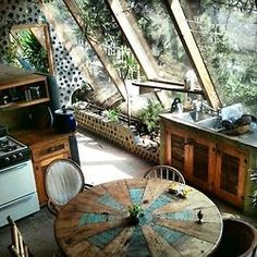 Earthy kitchen design, love the windows, the lights, round table rusticabode:earthship!