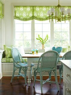 Cottage by the Sea: This Nantucket cottage brings all the wonders of the sea inside with splashes of bright color, lively seaside prints, and practical materials.     Blue painted wicker chairs paired with a white farmhouse table continue the breezy color palette. Fabric in a pale green pattern covers the window seat.