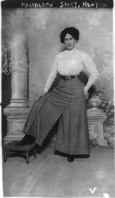 This is a female from 1910 wearing a pant suit. She has a white shirt with flared grey dress pants on.