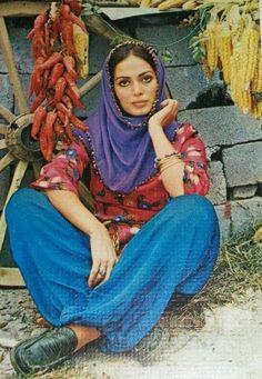 Türkan Şoray: royal purple headscarf, tied dark hair, magenta patterned blouse, royal blue maxi, black leather loafers; red peppers & yellow corn ears, wagon wheel & broken cinder blocks