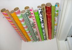gift wrap wired to the ceiling in a closet! Great use of a tiny space that would be unused!