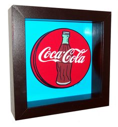 "This homage to the iconic Coca-Cola art Coke button makes the perfect addition to anyone's Coca-Cola collection. The artwork features the coke button rendered in 3-D, contrasting nicely against the blue background. The artwork comes framed in a black box frame and is hand-signed by the artist.    Dimensions: 5x5"" framed"