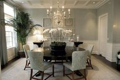 Pale blue/grey walls, bright white wainscotting, an arrangement of framed coral, coffered ceilings, a large dark wood round table, beautiful dining chairs upholstered in a light blue fabric, a gleaming metal chandelier make for a serenely luxurious dining room..