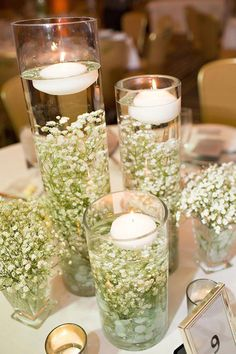 Look how pretty baby's breath looks submerged in water with floating candles on top. #weddingcenterpieceideas
