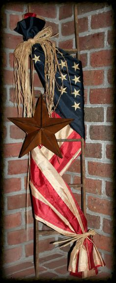 """Adorned with a tea-stained *replica* Americana flag and accented with a rusty star, this ladder will be a great addition to any Americana home decor or any front porch.  This American Flag ladder measures approx. 48"""" high."""
