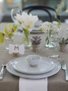 A contemporary table setting with white linen and stoneware dinner ...