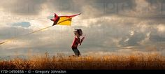 A panorama of a girl happily flying her kite