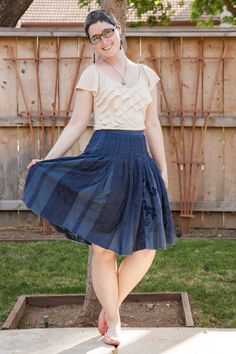 Ruffly cream tee, dark blue skirt, pink flats.