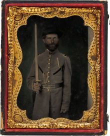 1861 Melainotype of a Confederate officer. Really, for quality, condition and content one of the finest Confederate images we've ever offered. Plate with embossed Melainotype patent information embossed along bottom edge, unquestionably dating the image to 1861. Officer wears gray frock coat with high standup collar, black flashing on edges of pocket on each breast and the shoulder straps appear to have black centers, possibly denoting North Carolina. Wears rather narrow brimmed slouch hat w...