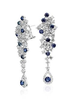 Fluid and elegant, these one of a kind drop earrings feature beautiful blue sapphire gemstones and diamonds set within a scattered drop design.