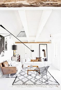 White living room with Moroccan rug, Bertoia Diamond chair, and ceiling beams. Bertoia Diamond Chairs Here: http://www.paletteandparlor.com/products/harry-bertoia-diamond-chair